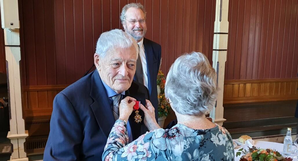 Svein Nordbotten får St. Olavs Orden festet på jakkeslaget av sin kone. Utmerkelsen ble overrakt av fylkesmann Lars Sponheim.
