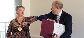 Ordfører Marte Mjøs Persen gir Rolf Reed en koronavennlig albuehilsen etter tildelingen av fortjenestemedaljen.