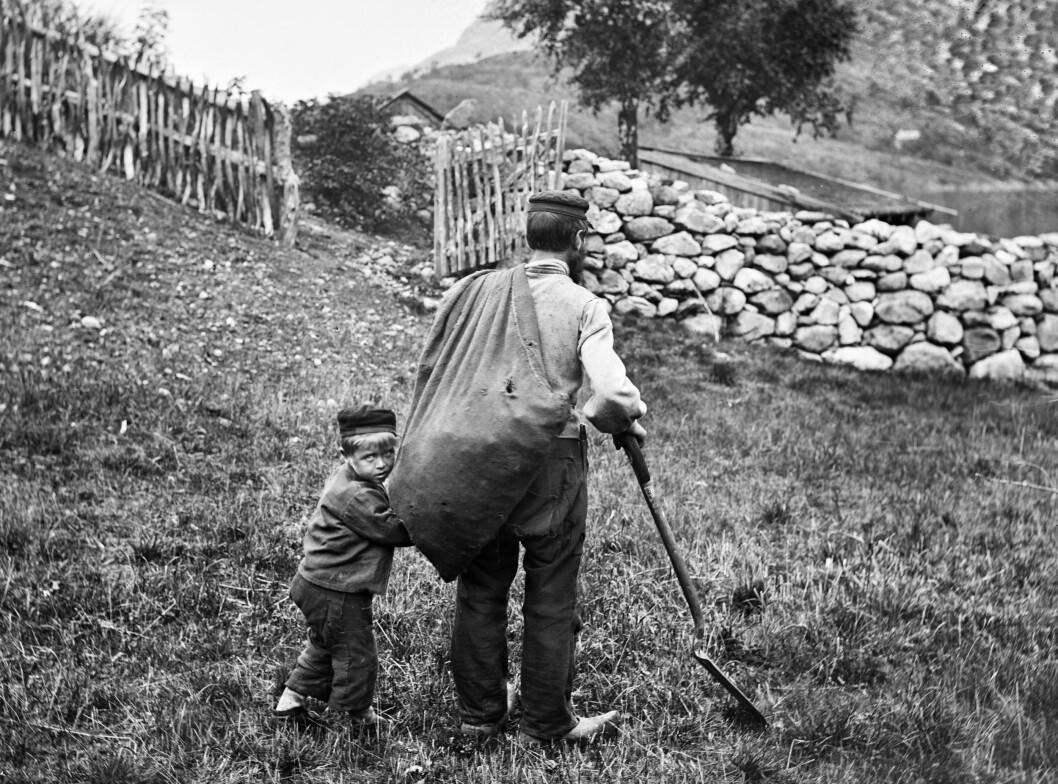 Liten gut på veg inn i kulturlandskapet, med undrande blikk og ei trygg hand å halda i. Fotografert på Tokheim, ca. 1870-1875.