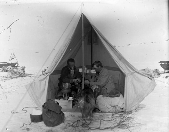 Johannes Persen, til venstre inni teltet, saman med ukjent assistent, 1912