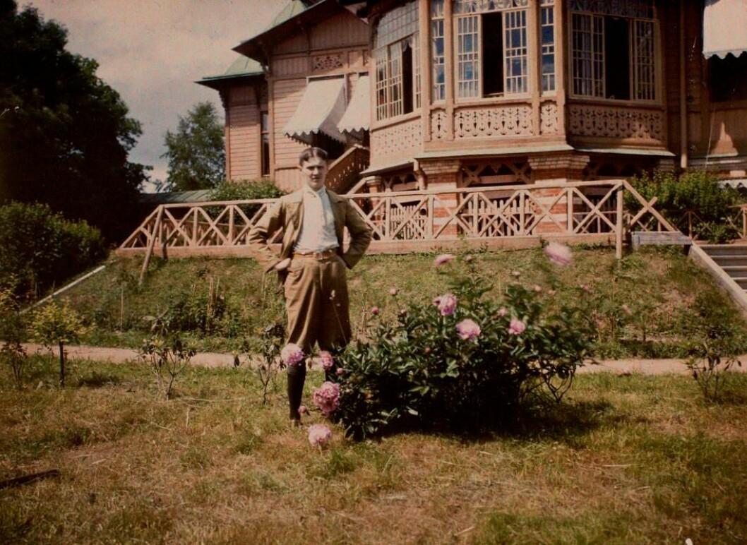 Ubb-knoop-397: Autokrom av Daniel G. Knoop. Fotografi av en ukjent mann foran et hus med treutskjæringer.